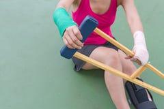 Tragender schmerzlicher Arm und Bein der Sportkleidung der Verletzungsfrau mit Gaze Stockfoto