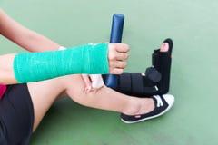 Tragender schmerzlicher Arm und Bein der Sportkleidung der Verletzungsfrau mit Gaze Stockbild