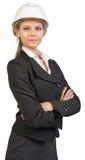 Tragender Schutzhelm der Geschäftsfrau, ihre Arme gekreuzt Stockbilder
