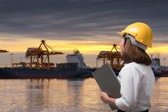 Tragender Schutzhelm des weiblichen Ingenieurs im Verschiffungshafen Lizenzfreies Stockbild