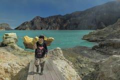 Tragender Schwefel des Bergmannes in einem Korb zur Försterstation an der Gebirgsspitze für das Wiegen, Indonesien stockfotos