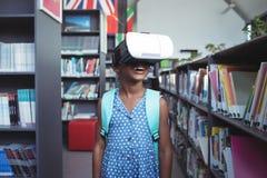 Tragender Simulator der virtuellen Realität des Mädchens in der Bibliothek stockfotografie