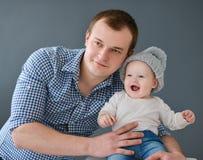 Tragender Sohn des glücklichen Vaters lokalisiert auf grauem Hintergrund Stockfoto
