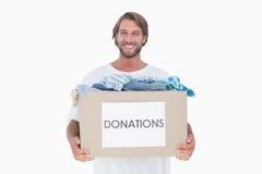 Tragender Spendenkasten des glücklichen Mannes Stockfotografie