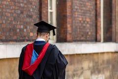 Tragender Staffelungshut und -kleid des graduierten Mannstudenten am Hochschullager lizenzfreies stockbild