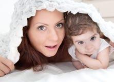 tragender strickender Hut und Mutter des Glücklich-aussehenden Babys, die toget spielen lizenzfreie stockbilder
