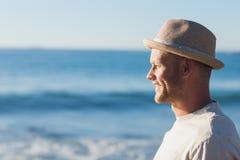 Tragender Strohhut des gutaussehenden Mannes, der das Meer betrachtet Stockfotografie
