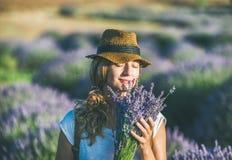 Tragender Strohhut des jungen Mädchens mit Blumenstrauß des Lavendels blüht Stockfotografie