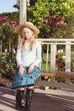 Tragender Strohhut des Mädchens im Garten stockfoto