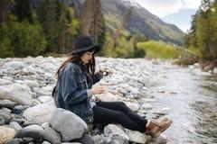 Tragender trinkender Tee des Rucksacks des Mädchens von der Thermosflasche und Betrachten des Sees stockfoto