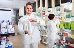 Tragender weißer Mantel des männlichen Apothekers, der in der Drogerie steht lizenzfreie stockfotos