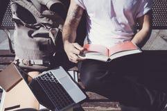 Tragender weißes T-Shirt des Nahaufnahmefotomannes sitzender Stadtpark und Lesebuch An der Universität studieren, Vorbereitung fü lizenzfreie stockfotografie