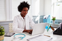 Tragender weißer Mantel der schwarzen Ärztin bei der Arbeit in einem Büro Stockfoto