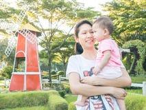 Tragendes Baby der asiatischen Mutter im Garten Lizenzfreie Stockfotos
