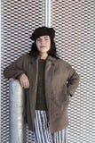 Tragendes Barett und Mantel des Brunettemädchens, die auf Metallspalte sich lehnen stockbild