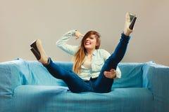 Tragendes Denim des modernen Mädchens, das auf Couch sitzt Lizenzfreie Stockbilder