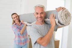 Tragendes des glücklichen Paars zusammen gerollt herauf Wolldecke Stockfotografie