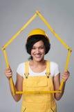 Tragendes Gelb des Frauenerbauers schützen den Sturzhelm und Gesamtes, die einen Hausrahmen zeigen Lizenzfreie Stockfotos