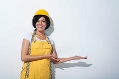 Tragendes Gelb des glücklichen Frauenerbauers schützen den Sturzhelm, der leeren Kopienraum zeigt Stockfotos