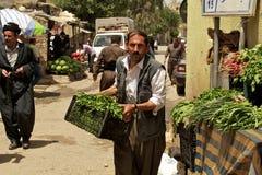 Tragendes Gemüse des Lebensmittelhändlers zu seinem Stand auf Basar (Markt) im Irak Stockbild