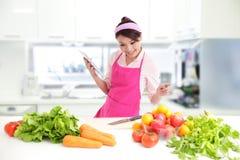 Tragendes Küchenschutzblech der jungen Frau mit Tablette lizenzfreie stockfotografie
