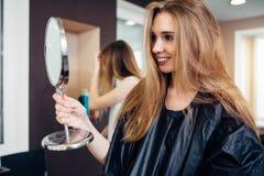 Tragendes Kap des jungen weiblichen Kunden, das einen Schminkspiegel schaut und lächelt im Schönheitssalon zufrieden gestellt mit stockfotografie