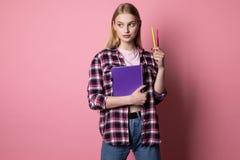 Tragendes kariertes Hemd der jungen netten Blondine, purpurrotes Notizbuch und Stift halten stockfotografie