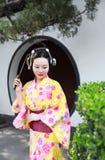 Tragendes Kimonospiel traditioneller asiatischer japanischer Frauenbraut Geisha in einem graden Griff ein Fan Lizenzfreie Stockfotografie