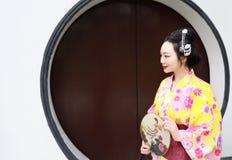 Tragendes Kimonospiel traditioneller asiatischer japanischer Frauenbraut Geisha in einem graden Griff ein Fan Stockfotografie
