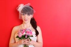 Tragendes Kleid der Braut und kurzer Schleier hält Blumenstrauß an Stockbild
