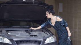 Tragendes Kleid der Schönheit versucht, ihr Luxusauto mit Schlüsseln zu reparieren stock video