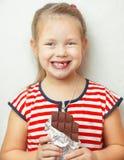 Tragendes Kleid des Mädchens mit Streifen und halten Schokolade Lizenzfreie Stockfotos