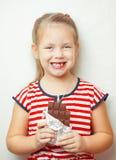 Tragendes Kleid des Mädchens mit Streifen und halten Schokolade Lizenzfreie Stockfotografie