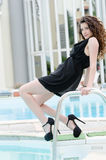Tragendes Kleid und Fersen der Frau sitzt auf Poolplattformtreppe Stockbild