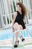 Tragendes Kleid und Fersen der Frau sitzt auf Poolplattformtreppe Lizenzfreies Stockbild