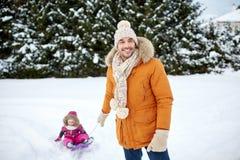 Tragendes Kleinkind des glücklichen Mannes auf Schlitten im Winter Stockbilder