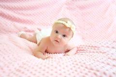 Tragendes Lügen des netten Babys auf Bauch auf weichem rosa Beschaffenheitshintergrund stockbild