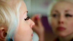 Tragendes Make-up des Mädchens der jungen Frau, stehend vor einem Spiegel Nahaufnahme stock video