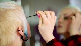 Tragendes Make-up des Mädchens der jungen Frau, stehend vor einem Spiegel Nahaufnahme stock video footage