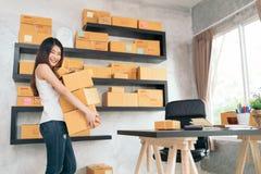 Tragendes Produkt des jungen asiatischen Kleinunternehmers packt zu Hause Büro, Online-Marketings-Verpackung und Lieferungsszene, lizenzfreies stockbild