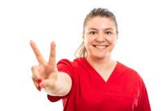 Tragendes Rot der jungen Arzthelferin scheuern das Zeigen des Friedenszeichens Stockfoto