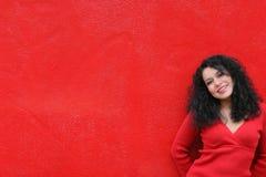 Tragendes Rot des Mädchens auf roter Wand Stockfotografie