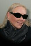 Tragendes Schal- und Sonnenbrillelächeln der blonden Frau Stockfotografie