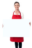 Tragendes Schutzblech Dame, das weißes leeres Anzeigenbrett hält stockbild