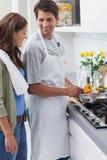 Tragendes Schutzblech und Kochen des Mannes Lizenzfreies Stockbild