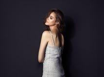 Tragendes silbernes Kleid des hübschen Brunette auf schwarzem Hintergrund Stockfotografie