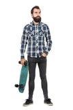 Tragendes Skateboard des überzeugten Hippies in einer Hand, die weg schaut Stockfoto