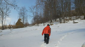 Tragendes Skikostüm des jungen Mannes, das einen Fußweg im Schnee am Berg herstellt stock video footage