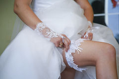Tragendes Strumpfband auf Bein der Braut Lizenzfreie Stockfotografie