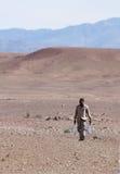 Tragendes Wasser des Mannes durch Wüste Stockfotografie